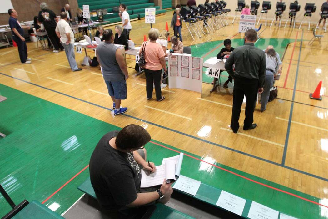 Adam Kerrigan, a volunteer poll observer, looks over the voter register at the Durango Hills YMCA, Tuesday, Nov. 6, 2012. Poll observers watch to make sure no irregularities occur at the polls. (J ...