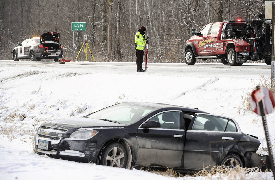 A Minnesota State Patrol trooper surveys the accident scene on Highway 218 Tuesday morning, Jan. 16, 2018 involving a car, foreground, and a semitrailer that left the road and collided with Lyle P ...