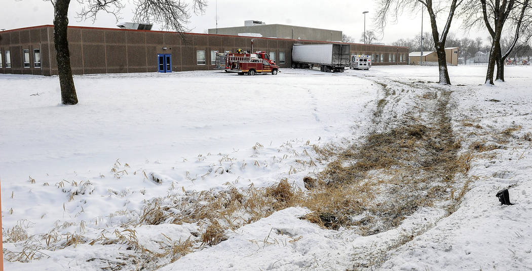A rough track leads to a semi, embedded in the side of Lyle Public School Tuesday morning, Jan. 16, 2018. The semi left Highway 218 in Lyle after trying to avoid a car making a turn, striking it i ...