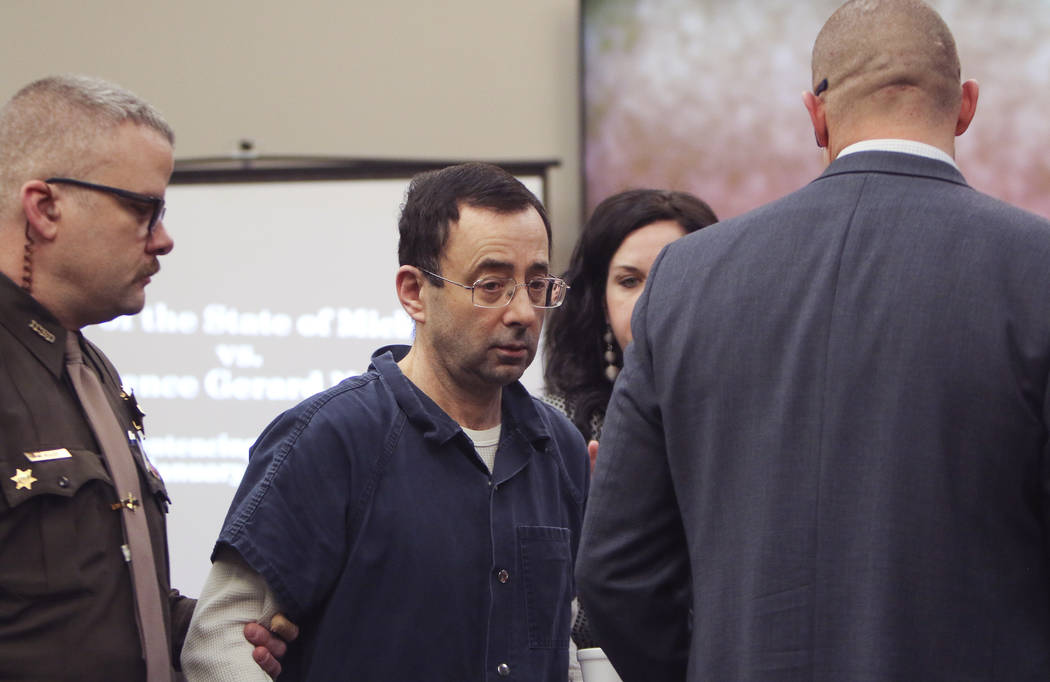 Larry Nassar arrives at court Tuesday, Jan. 16, 2018, for the first day of victim impact statements in Circuit Court Rosemarie Aquilina's courtroom in Lansing, Mich. Flanking Nassar are his attorn ...