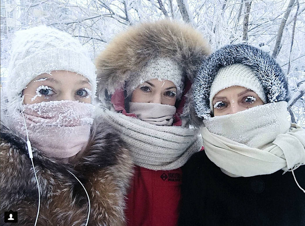 In this photo taken on Sunday, Jan. 14, 2018, Anastasia Gruzdeva, left, poses for selfie with her friends as the temperature dropped to about -50 degrees (-58 degrees Fahrenheit) in Yakutsk, Russi ...
