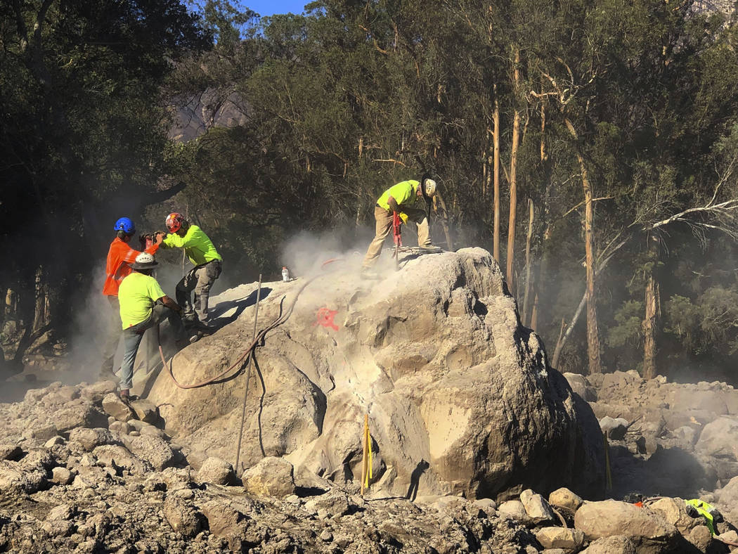 Demolition workers break down boulders Sunday, Jan. 14, 2018, that are scattered throughout Montecito, Calif., following the deadly mudslides containing rocks and debris that struck the area follo ...