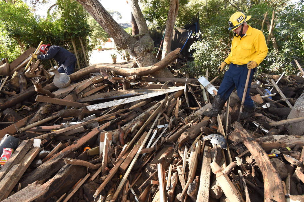 Santa Barbara County Fire Capt Adam Estabrook, left, and Engineer Rick Pinal search through a debris pile behind a Montecito, Calif., home, Jan. 13, 2018. The home was destroyed by deadly mudflow  ...