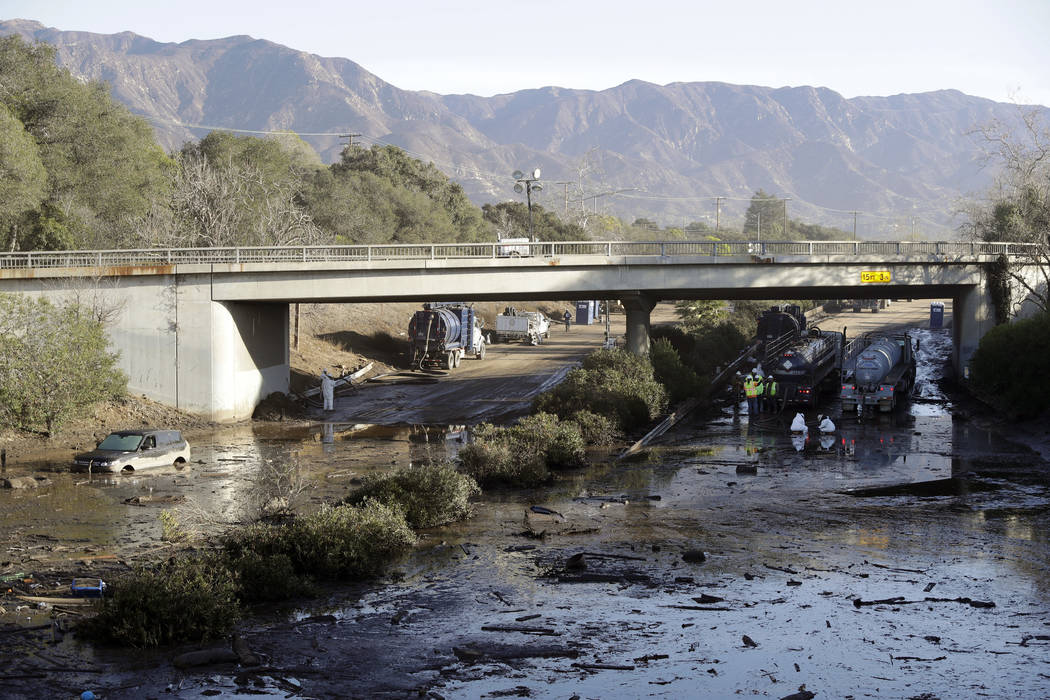 Crews work on clearing Highway 101 in the aftermath of a mudslide in Montecito, Calif., Jan. 13, 2018. Officials say the possibility of future catastrophic floods will be in mind as Montecito rebu ...