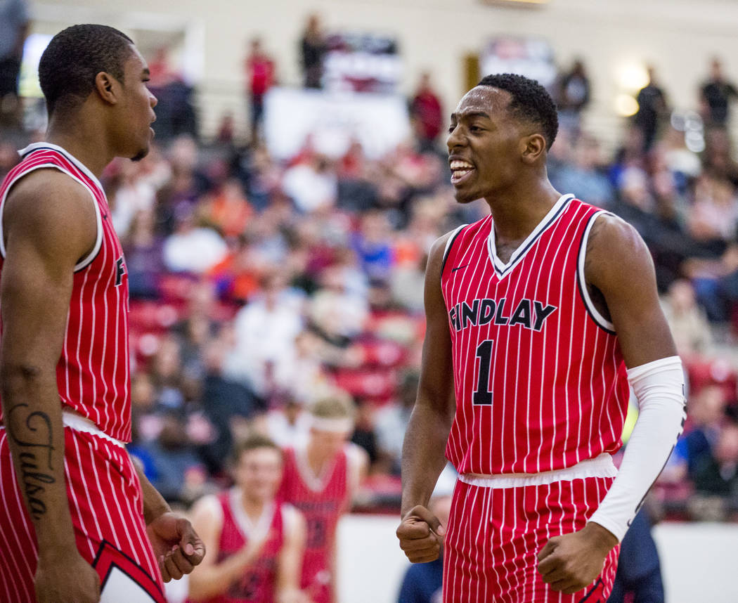 Findlay Prep's TJ Moss (1) celebrates with Reggie Chaney (20) after scoring during the Big City Showdown at South Point in Las Vegas on Saturday, Jan. 20, 2018. Findlay Prep won 75-68.  Patrick Co ...