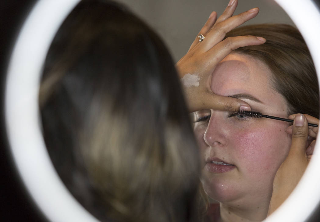 Make-up artist Paz Ramirez, left, applies an eyelash strip extension on Bekah Wachholz during the Bridal Spectacular wedding expo at the Rio Convention Center in Las Vegas on Sunday, Jan. 21, 2018 ...