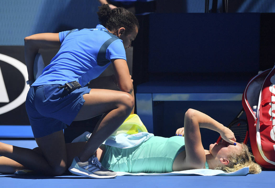 Katerina Siniakova of the Czech Republic receives treatment from a trainer while playing Ukraine's Elina Svitolina during their second round match at the Australian Open tennis championships in Me ...