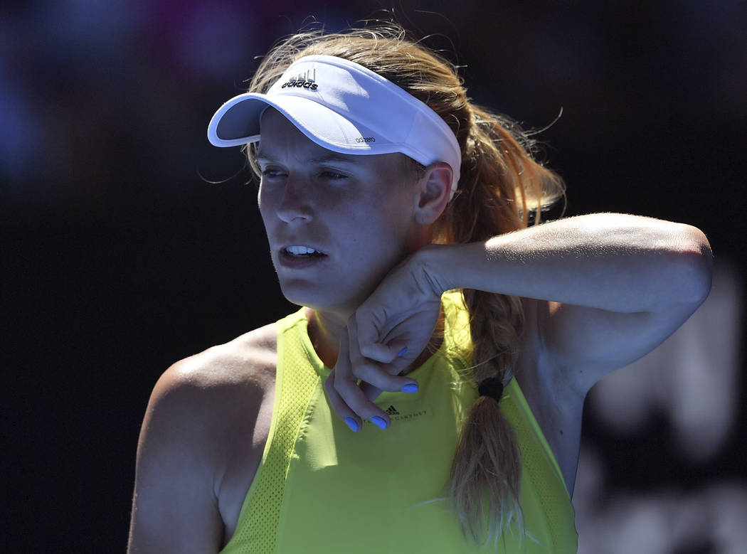 Denmark's Caroline Wozniacki wipes the sweat from her face while playing Croatia's Jana Fett during their second round match at the Australian Open tennis championships in Melbourne, Australia, We ...