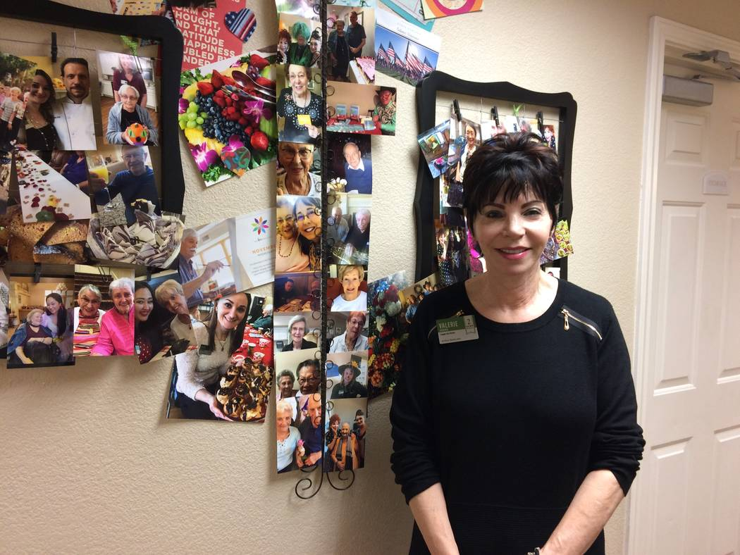 Valerie Howard stand by the resident activity photo wall Nov. 14, 2018. She has been the activities director for almost three years at Oakmont of West Las Vegas and keeps seniors busy with a pleth ...