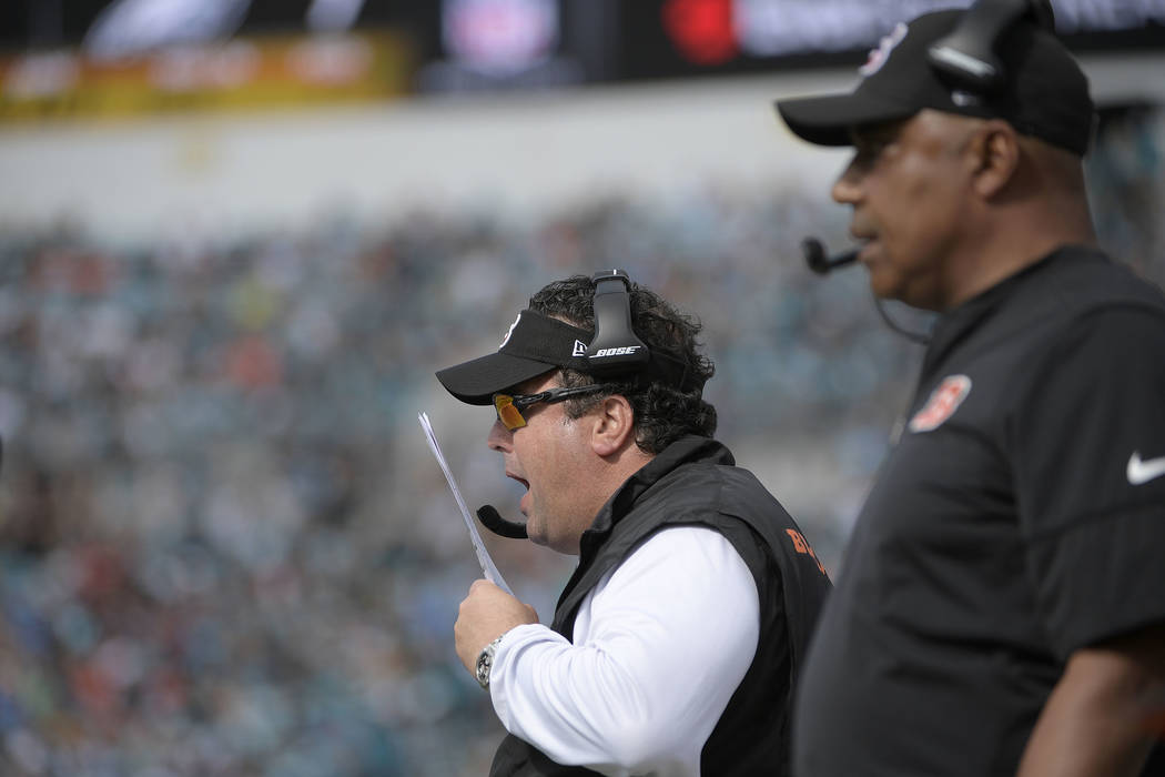 Former Cincinnati Bengals defensive coordinator Paul Guenther gives instructions from the sideline as head coach Marvin Lewis, right, watches during the first half of an NFL football game against  ...