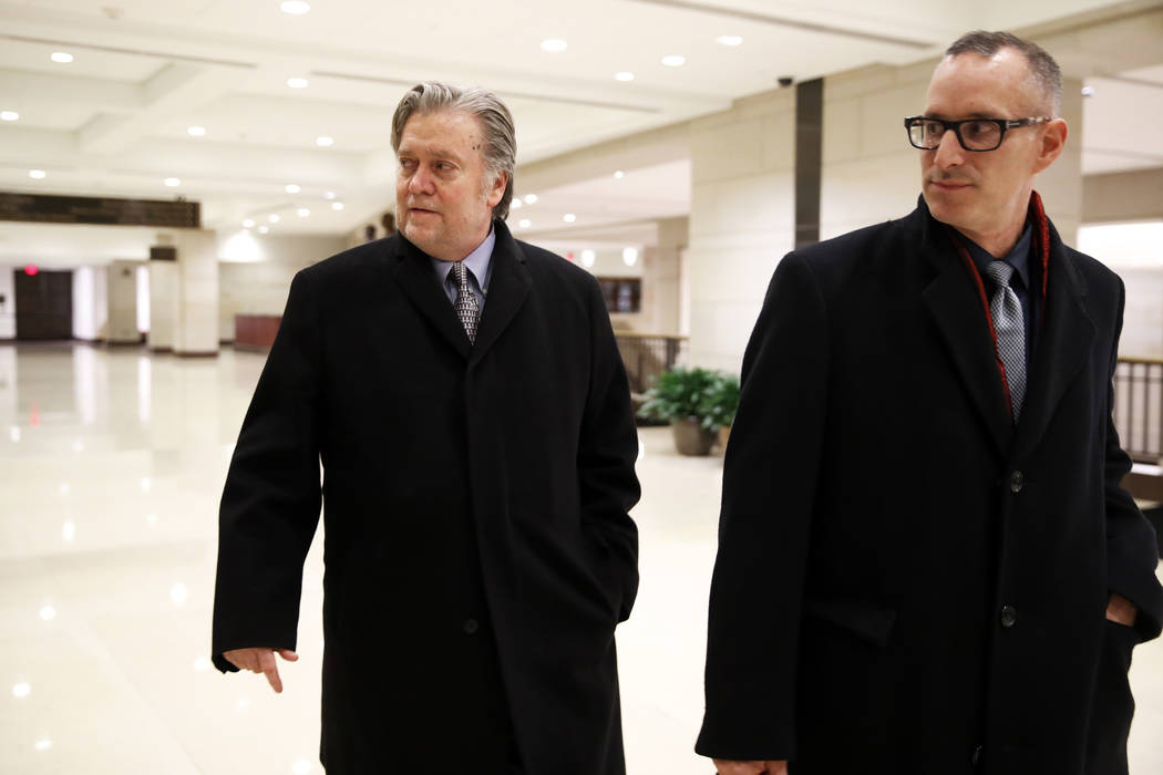 Former White House strategist Steve Bannon, left, leaves a House Intelligence Committee meeting where he was interviewed behind closed doors on Capitol Hill, Tuesday, Jan. 16, 2018, in Washington. ...