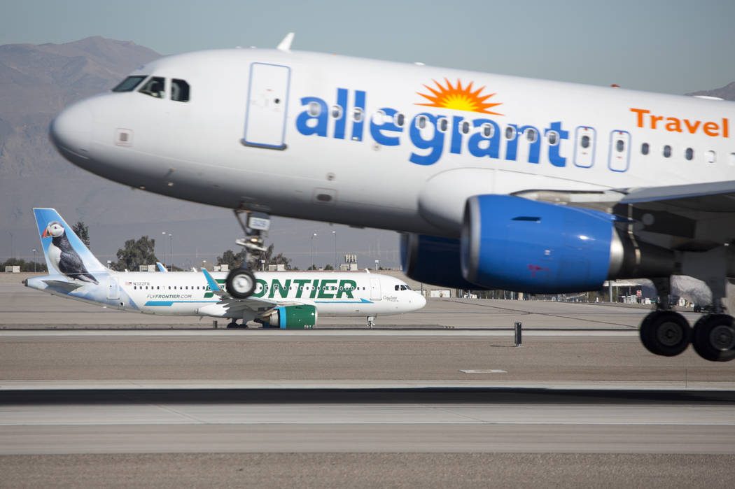 An Allegiant Air flight descends onto the runway as a Frontier Airlines aircraft taxis the tarmac at McCarran International Airport in Las Vegas on Monday, Jan. 22, 2018. Richard Brian Las Vegas R ...