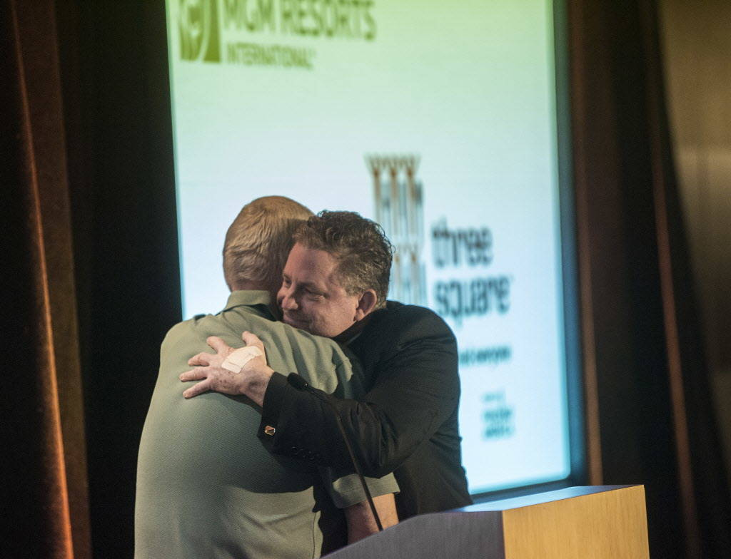 Deacon Tom Roberts, right, with Catholic Charities of Southern Nevada, hugs volunteer Andrew Hustak  during a media event to announce Three Square food bank's partnership with MGM Resorts Internat ...