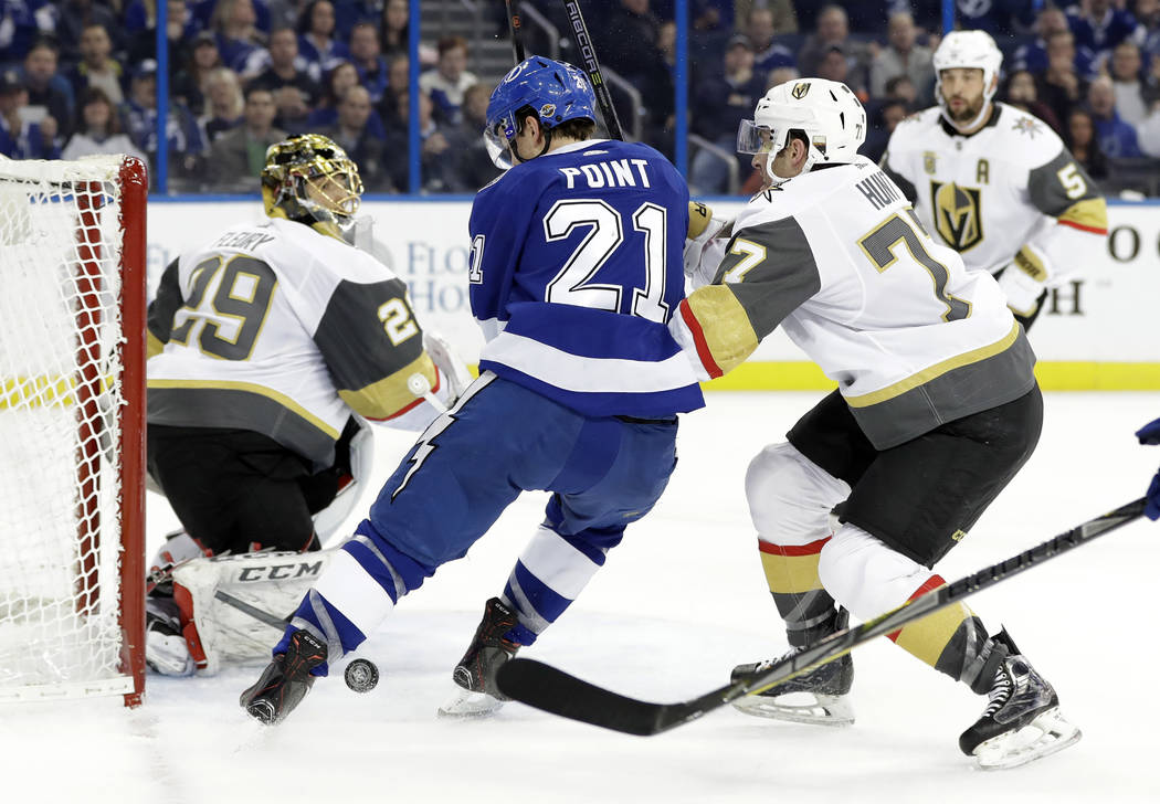 Vegas Golden Knights defenseman Brad Hunt (77) ties up Tampa Bay Lightning center Brayden Point (21) as he tries to score on goaltender Marc-Andre Fleury (29) during the second period of an NHL ho ...