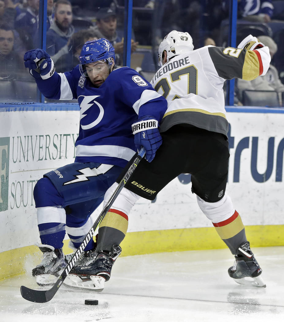 Tampa Bay Lightning center Tyler Johnson (9) and Vegas Golden Knights defenseman Shea Theodore (27) battle for the puck during the second period of an NHL hockey game Thursday, Jan. 18, 2018, in T ...