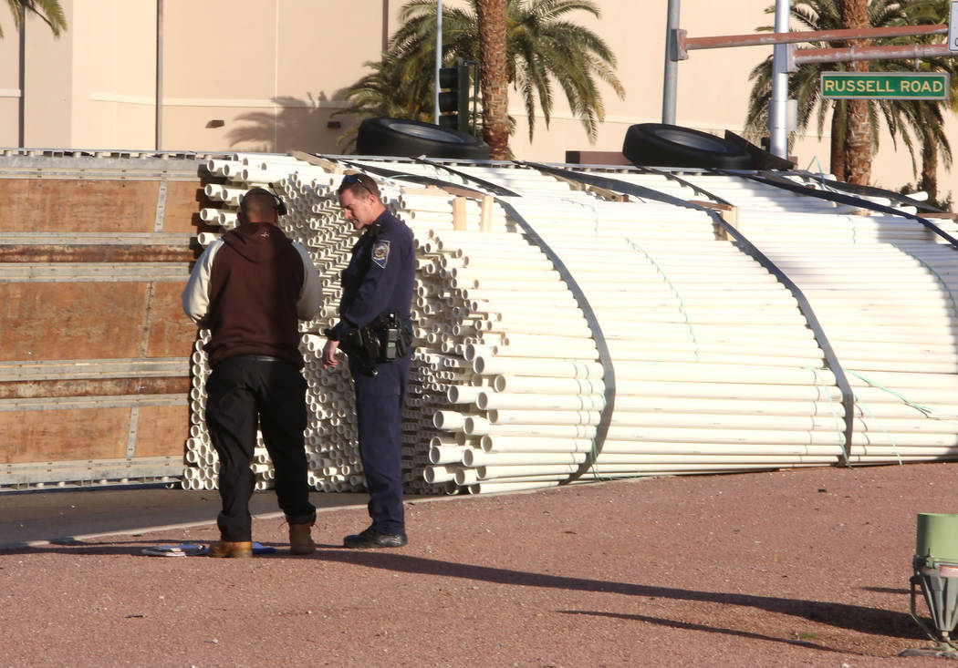 A semitrailer driver is questioned by a police officer at the scene of an accident where his truck overturned on Las Vegas Boulevard South at Russell Road on Thursday Jan. 18, 2017, in Las Vegas.  ...