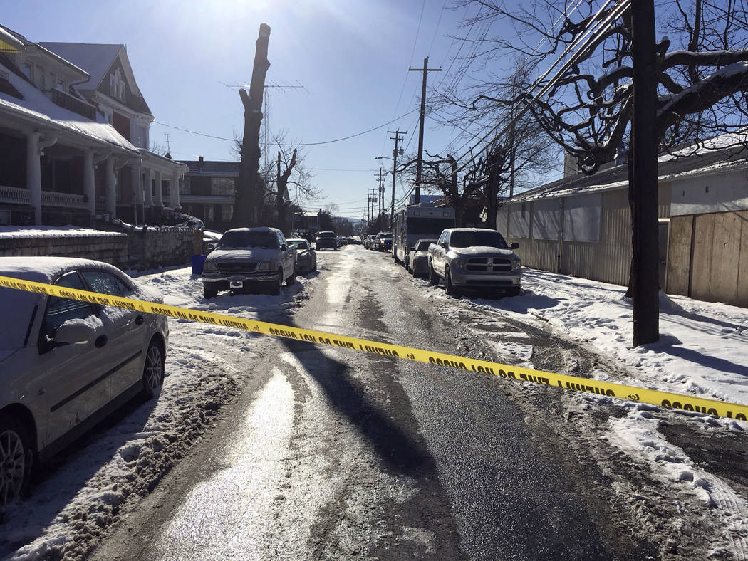 Crime tape stretches across a road near the scene of a shooting Thursday, Jan. 18, 2018, in Harrisburg, Pa. The mayor of Harrisburg said a U.S. marshal is dead after being shot while serving an ar ...