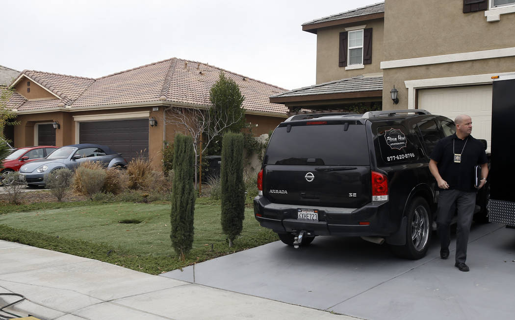 Detective walks next to a home Tuesday, Jan. 16, 2018, where police arrested a couple on Sunday accused of holding 13 children captive, in Perris, Calif. Authorities said an emaciated teenager led ...