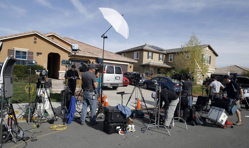 Members of the media work outside a home Tuesday, Jan. 16, 2018, where police arrested a couple on Sunday accused of holding 13 children captive, in Perris, Calif. Authorities said an emaciated te ...