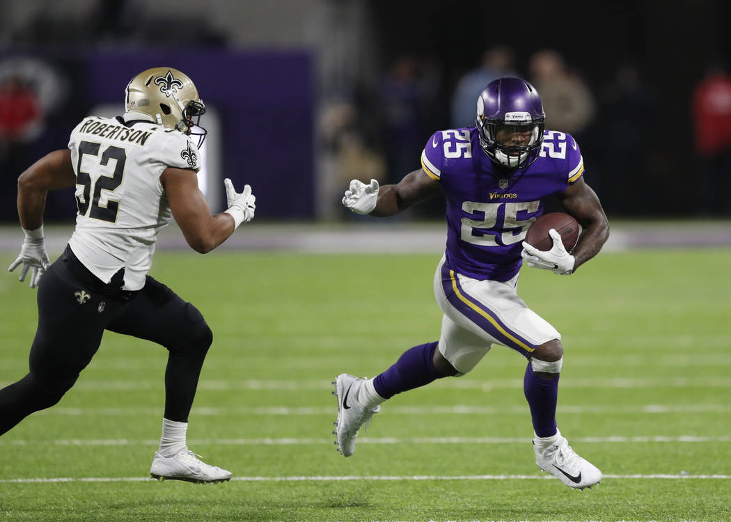 Minnesota Vikings running back Latavius Murray (25) runs around New Orleans Saints outside linebacker Craig Robertson (52) during the second half of an NFL divisional football playoff game in Minn ...