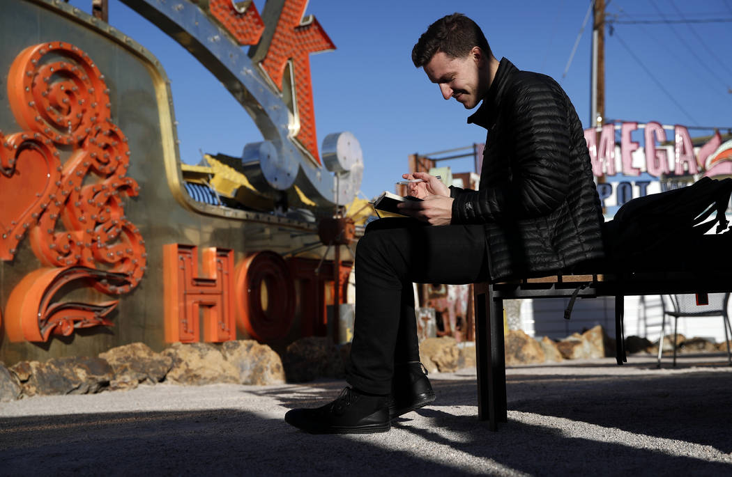 In this Jan. 23, 2018, photo, digital artist and designer Craig Winslow looks at his notebook at an exhibit at the Neon Museum in Las Vegas. Starting this week, visitors will be able to see many o ...