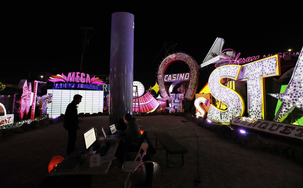 In this Jan. 24, 2018, photo, digital artist and designer Craig Winslow, left, works on an exhibit at the Neon Museum in Las Vegas. Starting this week, visitors will be able to see many of the cit ...