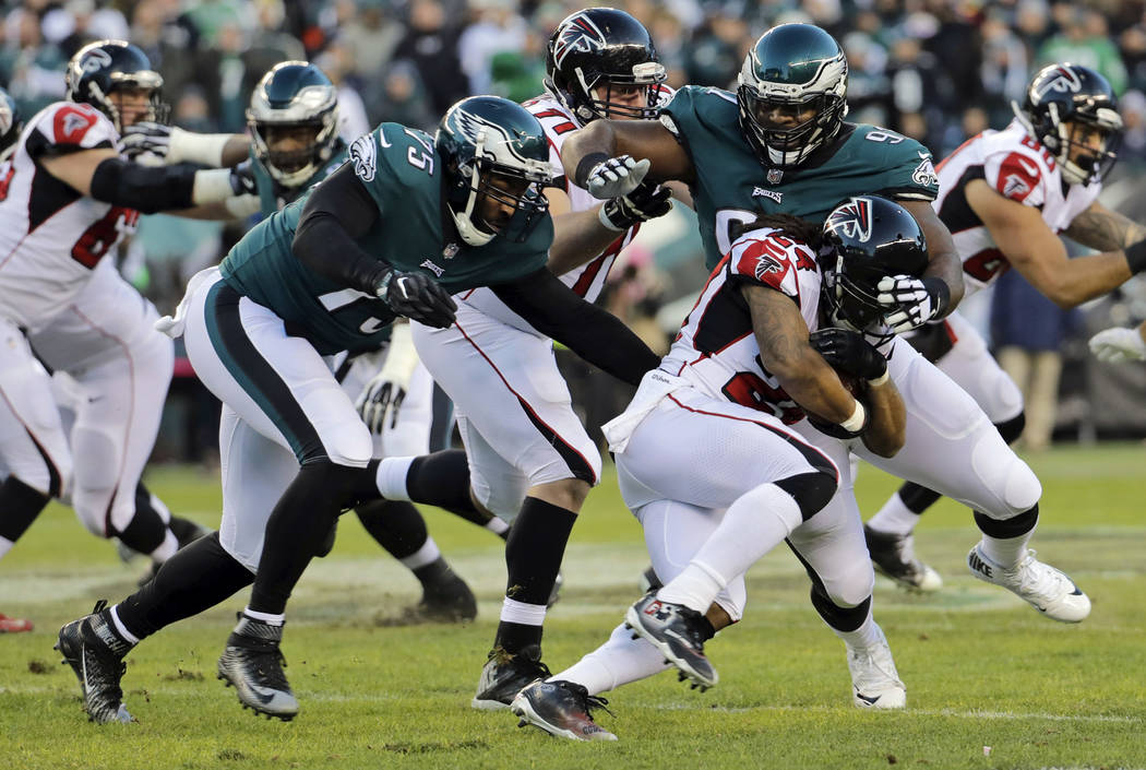 FILE- In this Saturday, Jan. 13, 2018, file photo, Philadelphia Eagles' Fletcher Cox (91) and Vinny Curry (75) close in on Atlanta Falcons' Devonta Freeman (24) during the first half of an NFL div ...
