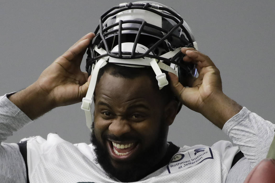 Philadelphia Eagles defensive tackle Fletcher Cox pulls on his helmet during practice at the team's NFL football training facility in Philadelphia, Thursday, Jan. 18, 2018. (AP Photo/Matt Rourke)