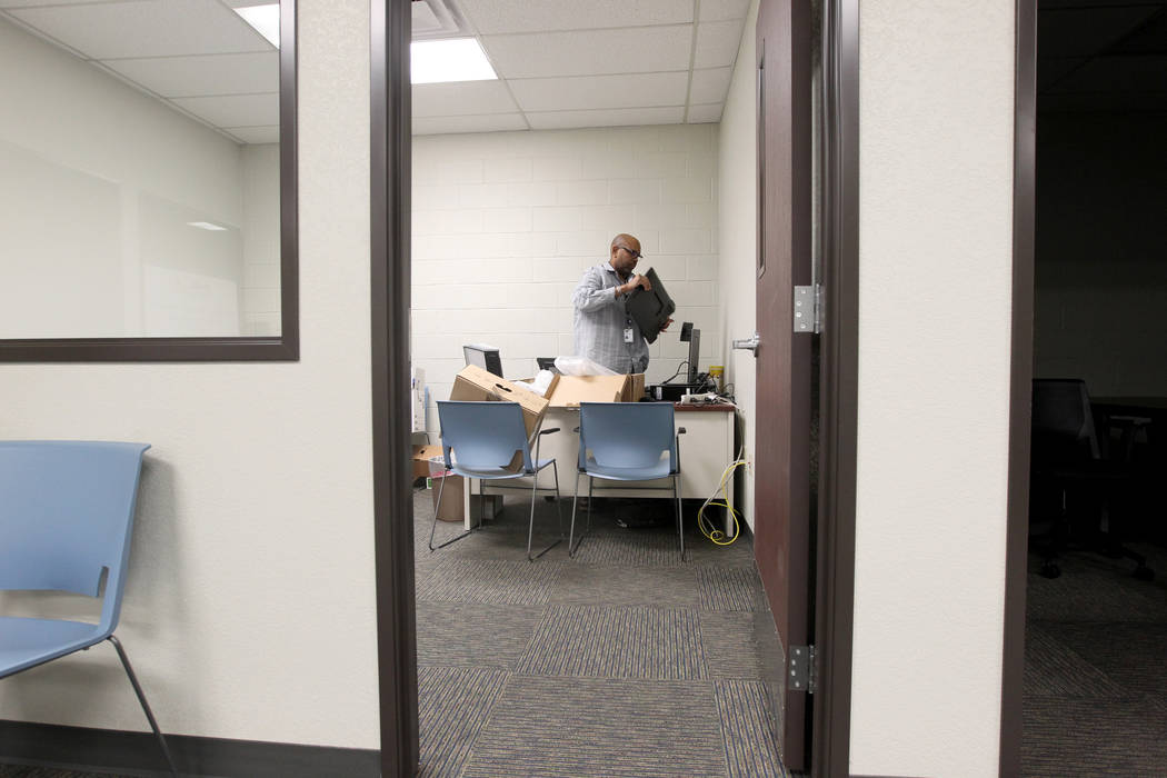 Everette Green with Clark County information technology department sets up a computer in the new location for The Harbor juvenile assessment center Friday, Jan. 19, 2018. The new location at 861 N ...