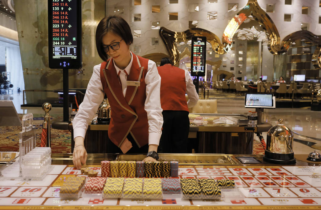 A croupier works at a gaming table at MGM Cotai Resort in Macau Tuesday, Feb.13, 2018. MGM Resorts is opening a lavish multibillion-dollar casino resort in Macau, in the latest big bet by foreign  ...