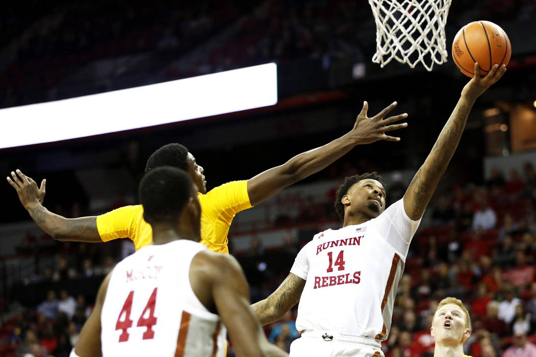 UNLV Rebels forward Tervell Beck (14) reaches for the ball during the basketball game against the Wyoming Cowboys at the Thomas and Mack Center in Las Vegas on Saturday, Feb. 10, 2018 as his teamm ...
