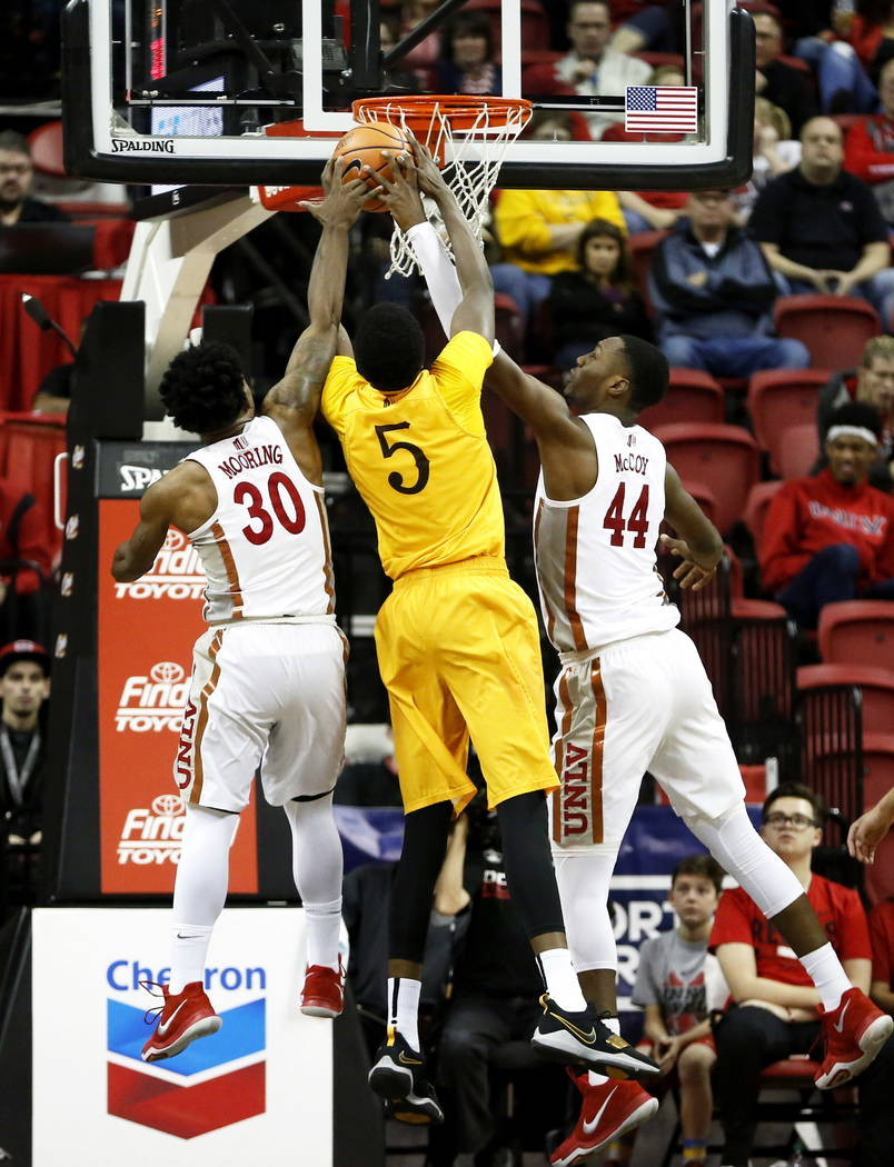 UNLV Rebels' Jovan Mooring (30) and Brandon McCoy (44) try to get the ball from the Wyoming Cowboys' Amin Adamu (5) at the Thomas and Mack Center in Las Vegas on Saturday, Feb. 10, 2018. Andrea Co ...
