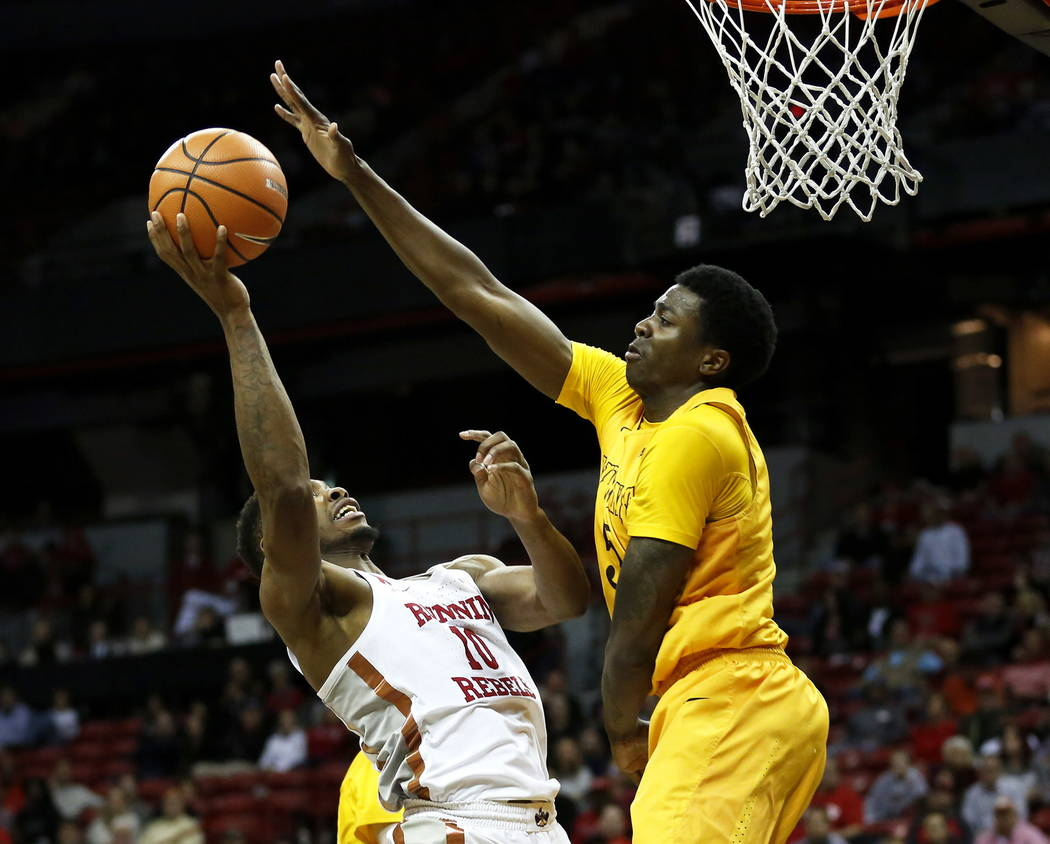 UNLV Rebels forward Shakur Juiston (10) shoots the ball while the  Wyoming Cowboys forward Alan Herndon (5) defends at the Thomas and Mack Center in Las Vegas on Saturday, Feb. 10, 2018. Andrea Co ...