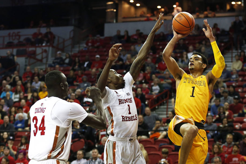 Wyoming Cowboys' Justin James (1) shoots the ball while UNLV Rebels' Cheikh Mbacke Diong (34) and Kris Clyburn (1) defend at the Thomas and Mack Center in Las Vegas on Saturday, Feb. 10, 2018. And ...