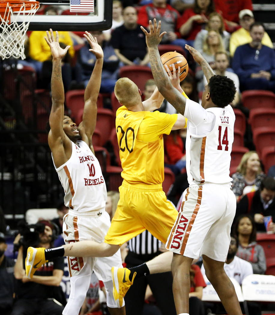 UNLV Rebels' Shakur Juiston (10) and Tervell Beck (14) try to get the ball from the Wyoming Cowboys' Hayden Dalton (20) at the Thomas and Mack Center in Las Vegas on Saturday, Feb. 10, 2018. Andre ...