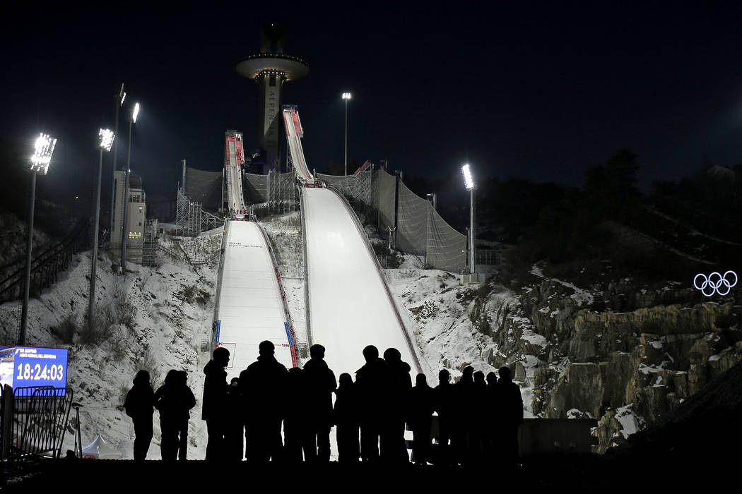 People wait for the start of practice for the men's ski jumping competition in the 2018 Winter Olympics at the Alpensia Ski Jumping Center in Pyeongchang, South Korea, Wednesday, Feb. 7, 2018. (AP ...
