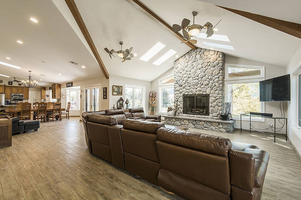 The family room has high, wood-beamed ceiling, skylights and a river rock fireplace. (Realty One Group)
