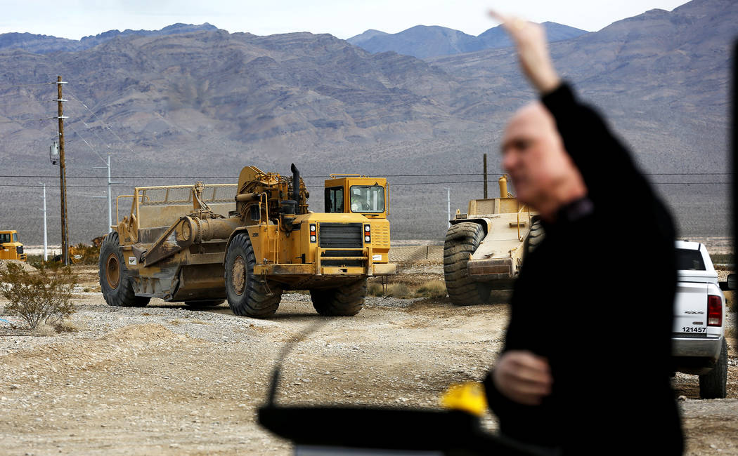 Construction continues while Clark County Commissioner Larry Brown talks to the crowd during the Nevada Department of Transportation's presser, which discussed the $65 million project aimed at imp ...