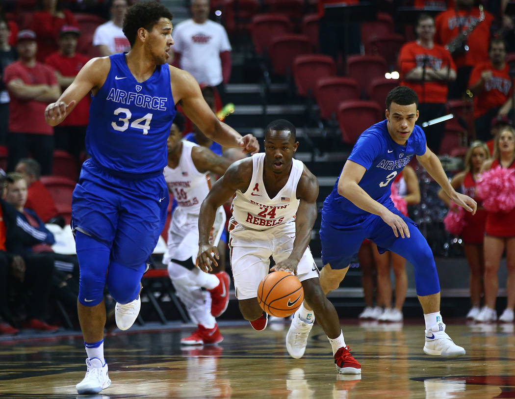 UNLV Rebels guard Jordan Johnson (24) brings the ball up court past Air Force Falcons forward Ryan Swan (34) and guard Sid Tomes (3) during a basketball game at the Thomas & Mack Arena in Las  ...