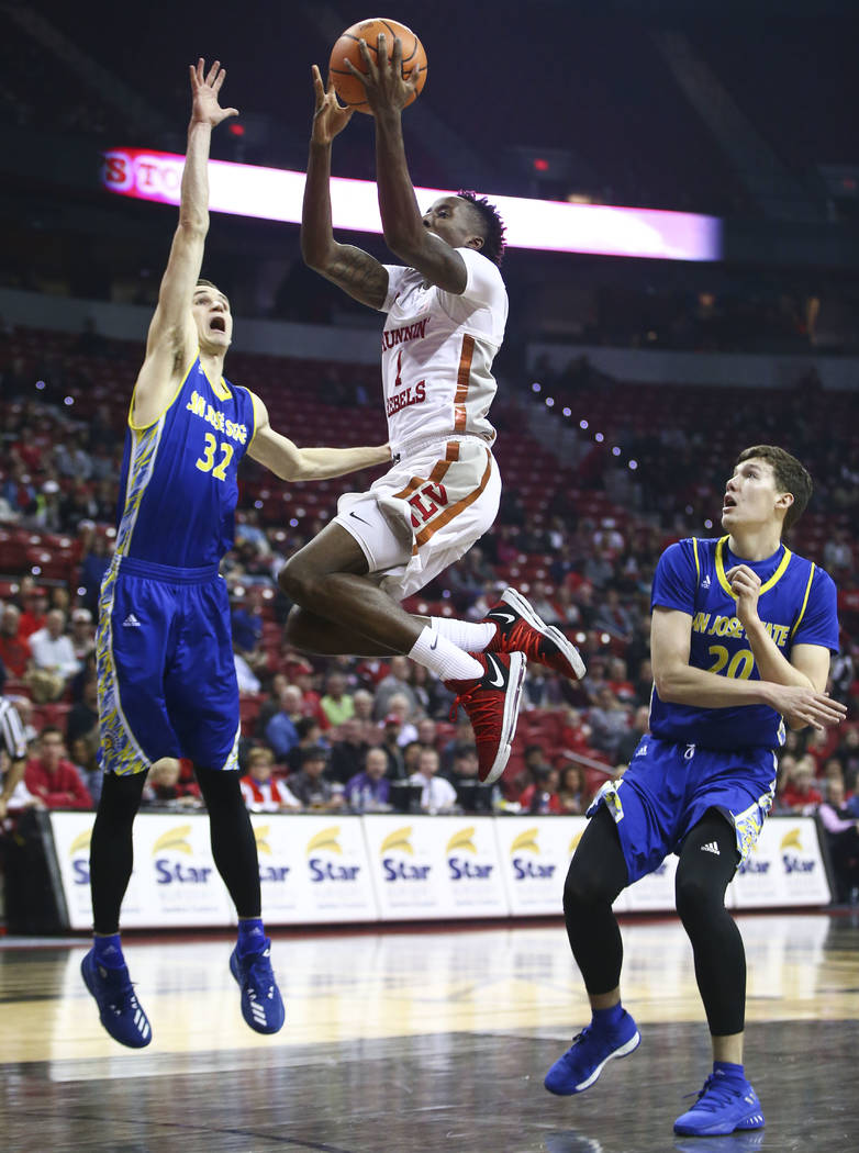 UNLV Rebels guard Kris Clyburn (1) goes to the basket between San Jose State Spartans forward Ryan Welage (32) and San Jose State Spartans guard Noah Baumann (20) during a basketball game at the T ...