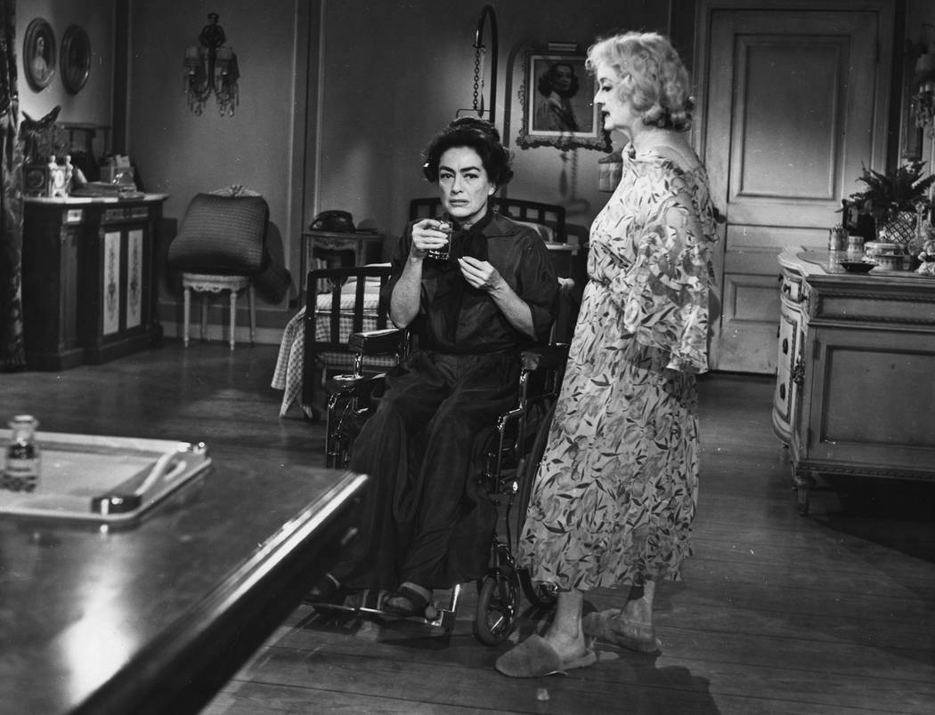 "Actress Joan Crawford, sits in wheelchair as actress Bette Davis stands next to her at the set in a scene while filming ""What Ever Happenend To Baby Jane"" in Hollywood, USA, Augu ..."