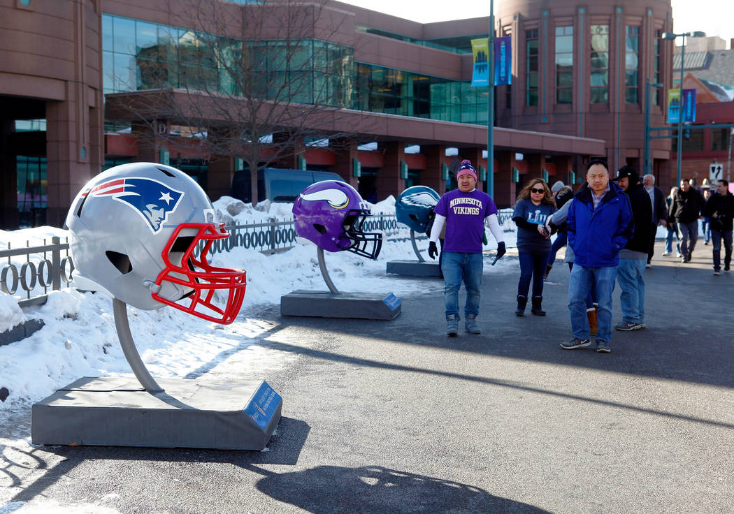 Fans check out the Philadelphia Eagles helmet, right, the New England Patriots helmet, left, and the Minnesota Vikings helmet as they head towards the NFL Experience at the Minneapolis Convention  ...