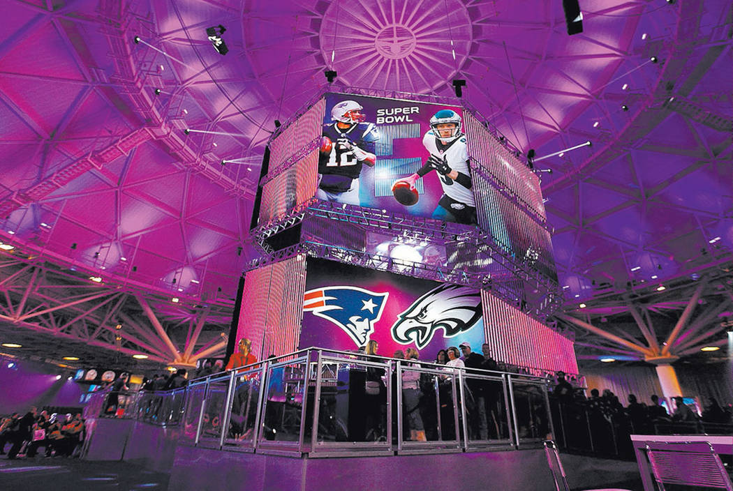 A banner featuring New England Patriots quarterback Tom Brady, left, and Philadelphia Eagles quarterback at the NFL Experience at the Minneapolis Convention Center in Minneapolis, Minn., Friday, F ...