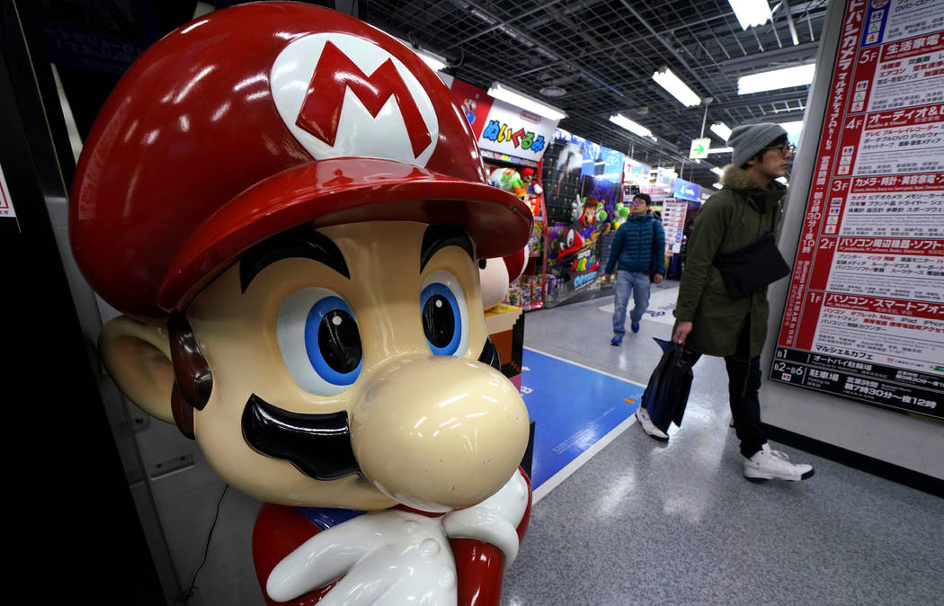 A Super Mario figure greets shoppers at an electronics store in Tokyo, Wednesday, Jan. 31, 2018. Japanese video-game maker Nintendo says its net profit jumped 31 percent in April-December from a y ...