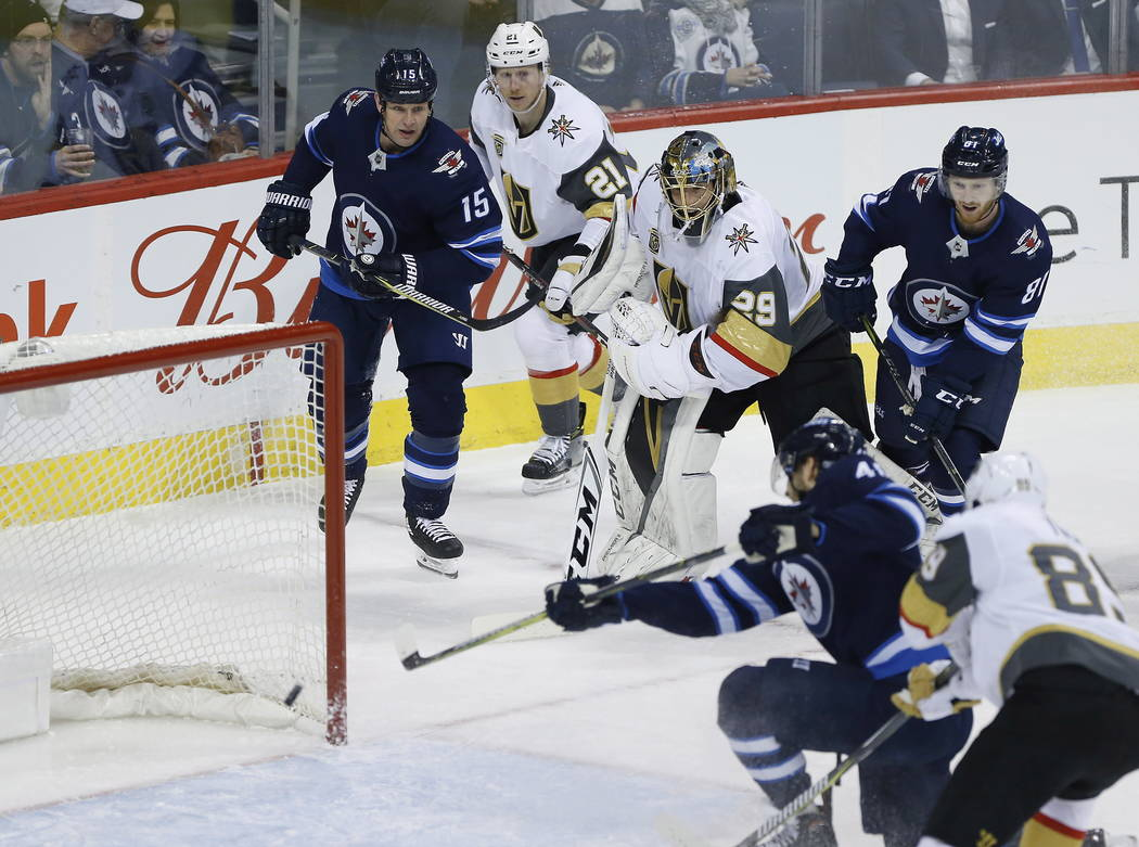 Vegas Golden Knights goaltender Marc-Andre Fleury (29) gets caught out of his net and watches Winnipeg Jets' Joel Armia (40) converts Matt Hendricks' (15) pass into a goal during the first period  ...