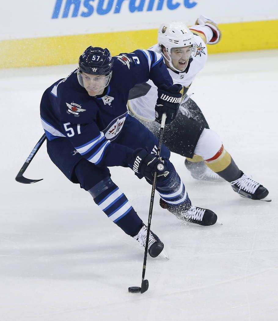 Winnipeg Jets' Tyler Myers (57) avoids Vegas Golden Knights' Brendan Leipsic (13) dduring the first period of an NHL hockey game Thursday, Feb. 1, 2018, in Winnipeg, Manitoba. (John Woods/The Cana ...
