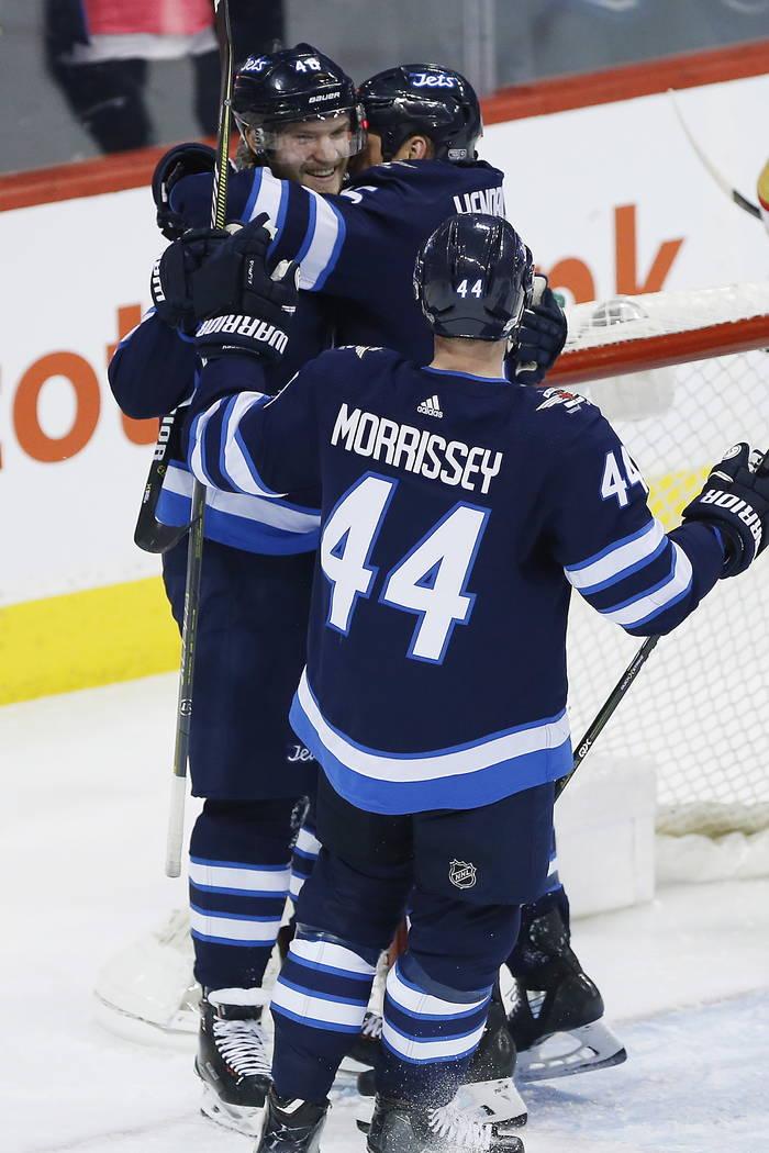 Winnipeg Jets' Joel Armia (40), Matt Hendricks (15) and Josh Morrissey (44) celebrate Armia's goal against the Vegas Golden Knights during the first period of an NHL hockey game Thursday, Feb. 1,  ...
