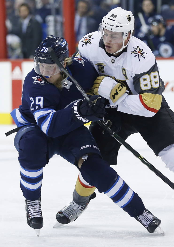 Vegas Golden Knights' Nate Schmidt (88) and Winnipeg Jets' Patrik Laine (29) collide during the second period of an NHL hockey game Thursday, Feb. 1, 2018, in Winnipeg, Manitoba. (John Woods/The C ...