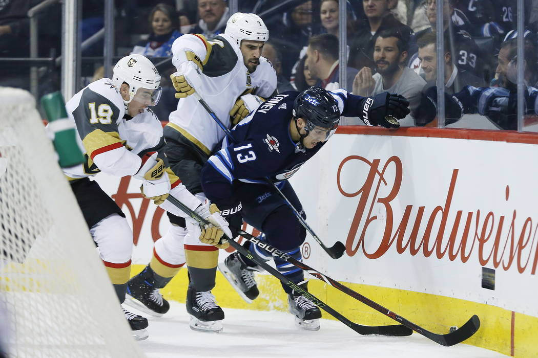 Winnipeg Jets' Brandon Tanev (13) fights for the puck against Vegas Golden Knights' Reilly Smith (19) and Jason Garrison (7) during the second period of an NHL hockey game Thursday, Feb. 1, 2018,  ...