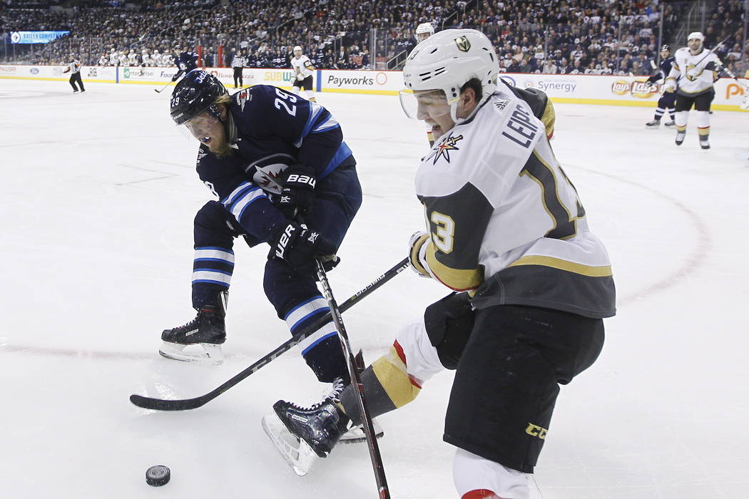 Winnipeg Jets' Patrik Laine (29) and Vegas Golden Knights' Brendan Leipsic (13) fight for possession of the puck during the second period of an NHL hockey game Thursday, Feb. 1, 2018, in Winnipeg, ...